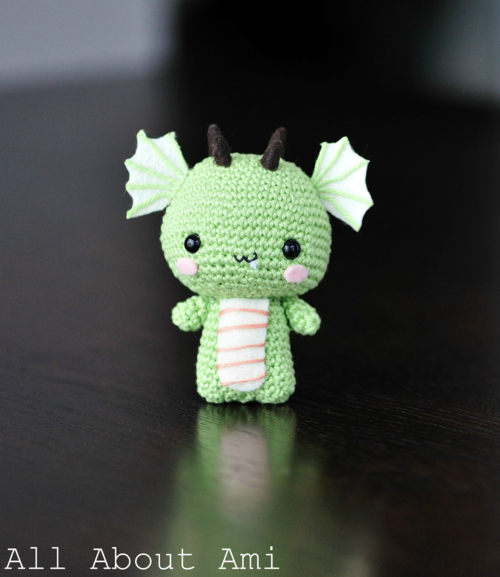 a small green crochet amigurumi dragon
