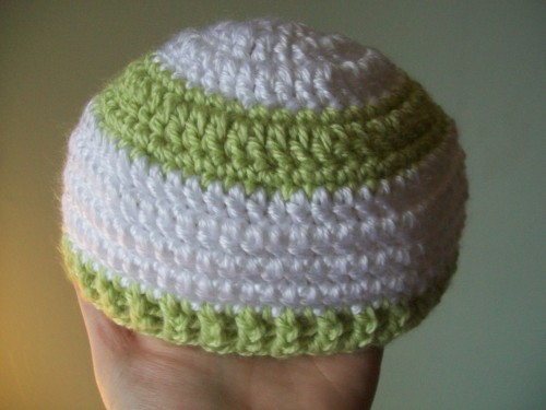 a crochet newborn baby hat with strips and a ribbed edging