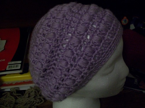 a purple crochet puff stitch slouch beanie child size made with acrylic yarn side view