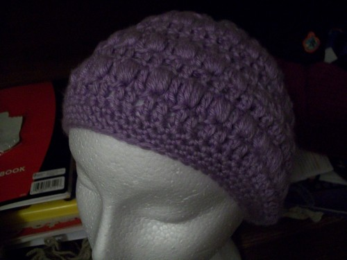a purple crochet slouch beanie child size made with acrylic yarn